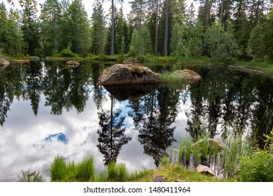 Pond in the forest of Sweden with reflections in the water, region Dalarna nearby Fredriksberg