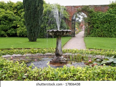 Pond and Fountain in an English Garden and archway through a wall