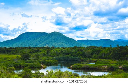Pond in a green landscape with mountains in the background and a blue sky with clouds - Itapema - Santa Catarina - Brasil