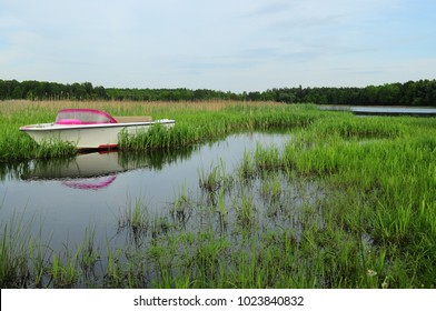 Pond Pond with a motorboat in the bushes. Beautiful summer weather, peace and relaxation.