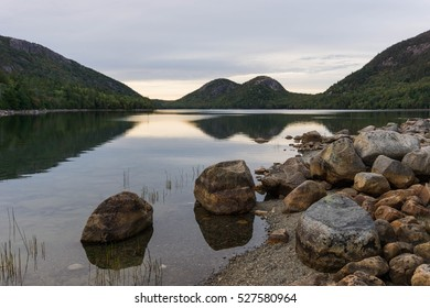 pond with mountains and reflection and rocks in the foreground