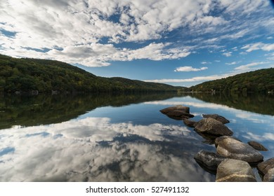 pond with reflection of sky and clouds and rocks in the foreground in New England