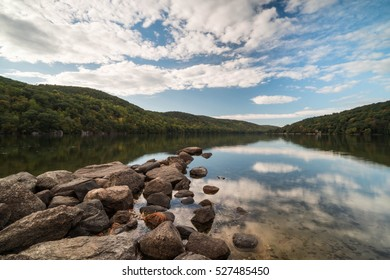 pond with rocks and cloud reflection and forest in New England