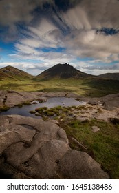 Pond of water up in the Mourne mountains in Northern Ireland with blue cloudy sky in background and rocks in foreground