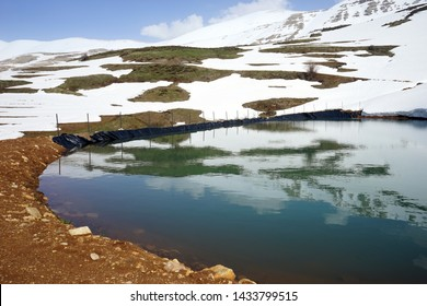 Pond with water and snow mountain near Quadisha valley in Lebanon
