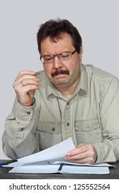 Ponderer man portrait near the desk on gray background