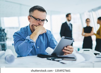 Pondering 50 years old male entrepreneur in trendy eyewear reading received email with bad news about finance problems feeling puzzled on solving, concept of technology and communication