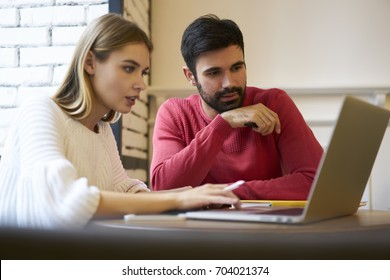 Pondering beautiful blonde woman and handsome bearded male colleagues carefully watching video on laptop computer connected to 4G internet.Couple in love using modern technology during sitting in cafe