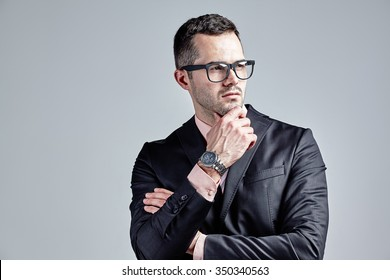Pondering businessman with hand at chin isolated over grey