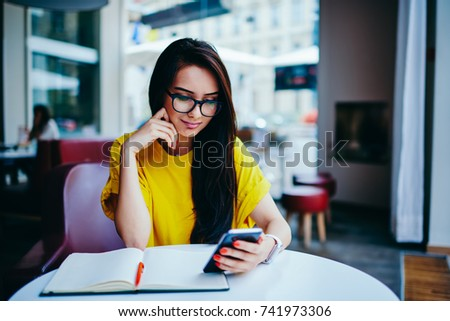 5730b750628 Pondering charming woman in cool eyeglasses watching interesting video in  website on smartphone connected to 4G