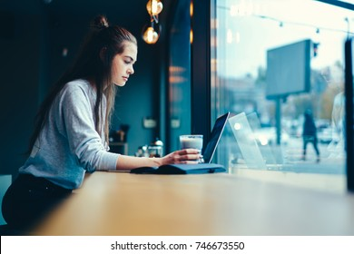 Pondering talented graphic designer carefully watching training webinar in website on laptop computer connected to internet.Young pretty hipster girl remotely working on gadget in coffee shop