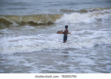 PONDICHERRY, INDIA 28 JULY 2015 : Unidentified Local children playing with surf at the seashore on beach in morning.