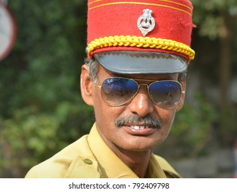 PONDICHERRY, INDIA - FEB 21, 2016: Indian senior policeman from Pondicherry (Puducherry) with sunglasses wears traditional red French-style police kepi and poses for the camera, on Feb 21, 2016.