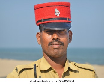 PONDICHERRY, INDIA - FEB 21, 2016: Indian policeman from Pondicherry (Puducherry) wears traditional red French-style police kepi and poses for the camera at the beach, on Feb 21, 2016.