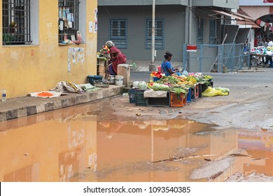 Pondicherry, India - March 17, 2018: An unidentified fruit and vegetable seller awaiting customers at the roadside after heavy rainfall