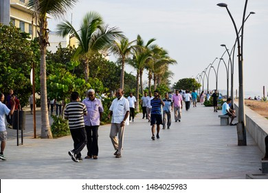 Pondicherry, Puducherry, Tamil Nadu 2019 : Healthy People walking on street and greeting each other on a pathway located near sea beach. The pathway is surrounded by trees and equipped with poles