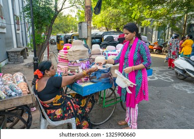 Pondicherry,Puducherry,February,19,2019: Woman street vendor using hand cart to sell gift items,caps and hats  as souvenirs  on street of Puducherry,India,Asia,