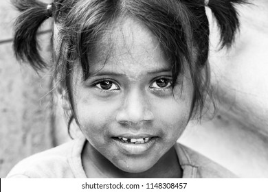 PONDICHERY, PUDUCHERRY, TAMIL NADU, INDIA - SEPTEMBER CIRCA, 2017. Portrait of unidentified Indian poor kid child girl is smiling outdoor in the street/ Black and white