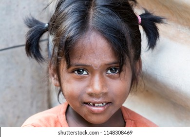 PONDICHERY, PUDUCHERRY, TAMIL NADU, INDIA - SEPTEMBER CIRCA, 2017. Portrait of unidentified Indian poor kid child girl is smiling outdoor in the street
