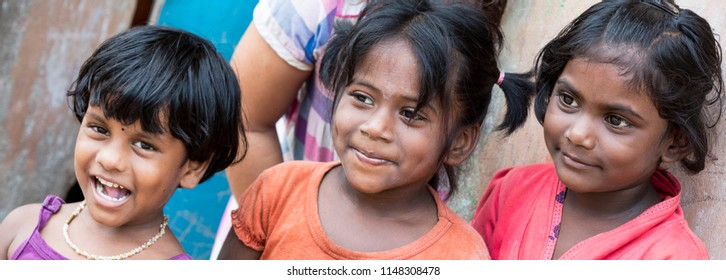 PONDICHERY, PUDUCHERRY, TAMIL NADU, INDIA - SEPTEMBER CIRCA, 2017. Portrait of 3 unidentified Indian poor kid child girl is smiling outdoor in the street.