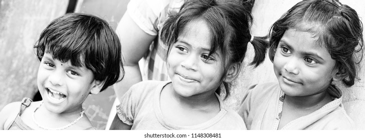 PONDICHERY, PUDUCHERRY, TAMIL NADU, INDIA - SEPTEMBER CIRCA, 2017. Portrait of 3 unidentified Indian poor kid child girl is smiling outdoor in the street/ Black and white
