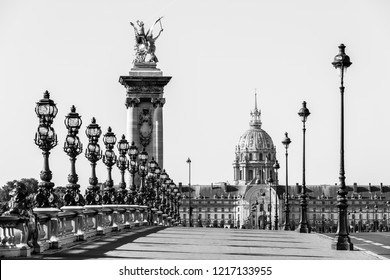 Pont Alexandre III bridge over the River Seine and the Hotel des Invalides in the background in the sunny summer morning. Bridge decorated with ornate Art Nouveau lamps and sculptures. Paris, France