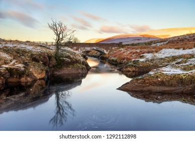 Pont Ar Elan,  Elan Valey, wales snowy scene of Afon Elan flowing through a bridge in winter with lone tree reflected in water and early morning sun lighting the top of distant mountains