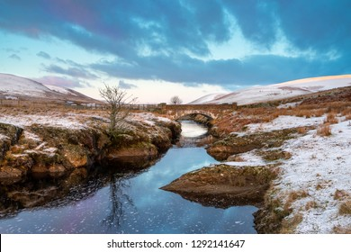 Pont Ar Elan, Elan valley, wales. Snowy scene of Afon elan flowing under a bridge with lone tree and early sun
