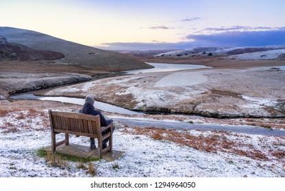 Pont Ar Elan, Elan valley, wales. Snowy scene of Afon elan flowing around mountain with hiker sitting on a bench admiring the view