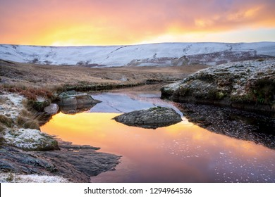 Pont Ar Elan, Elan valley, wales. Snowy scene of Afon elan flowing towards craig goch under orange sunrise with reflection of sky