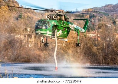 PONT CANAVESE, TURIN - November 30, 2017.Erickson Air Crane Sikorsky  S-64, Orso Bruno, during charging water from a river to  firefighting operation near Turin, Italy. Big helicopter vigili del fuoco
