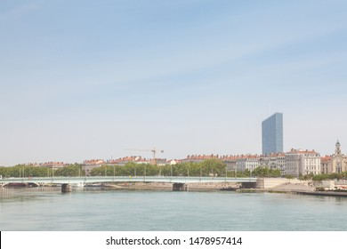 Pont de la Guillotiere bridge in Lyon, France over a panorama of the riverbank of the Rhone river (Quais de Rhone) with older buildings and a modern skyline in background