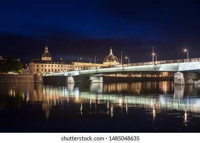 Pont de la Guillotiere bridge in Lyon, France over a panorama of the riverbank of the Rhone river (Quais de Rhone) at night with the main monuments of the old Lyon in background