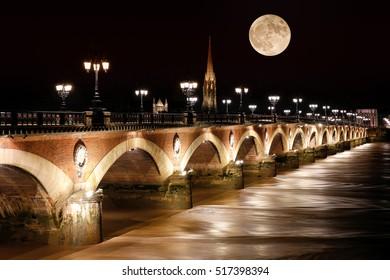 Pont de Pierre stone bridge with supermoon, Bordeaux, France