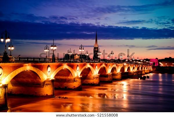 Pont de Pierre, pont de pierre sur la rivière garonne à Bordeaux, France au coucher du soleil avec l'église st michel en arrière-plan