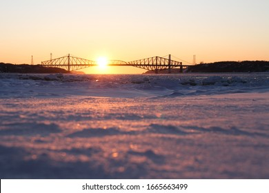 Pont de Quéebec, Quebec old Cantilever bridge in winter at sunset taken from the ground. Ice and snow covering the Saint Lawrence river, Levis, Quebec, Canada