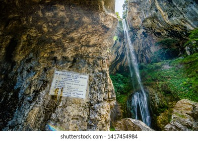 Pont du Loup, France - June 20, 2018. Waterfall Cascade de Courmes near Pont du Loup. Historic information board about tunnel and road construction in year 1904-1906