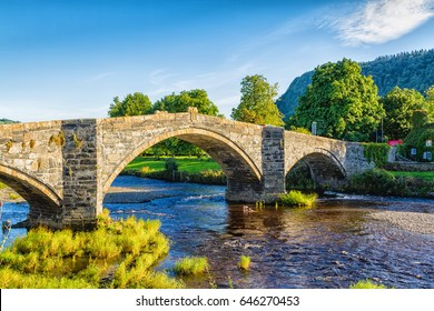 Pont Fawr, famous medieval stone bridge across the river Conwy, built by Inigo Jones, and Tu-Hwnt-l'r Bont - old cottage covered with vine leaves, Llanrwst, Caernarfon, North Wales, United Kingdom