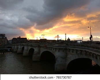 PONT NEUF, PARIS/FRANCE - DECEMBER 2017: Side view of pont neuf during late afternoon, sunset with cloudy day over Sena river bridge in Paris/France