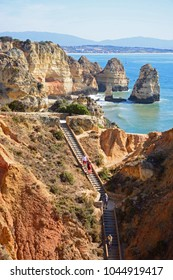 PONTA DA PIEDADE, PORTUGAL - JUNE 8 2017 - Elevated view of the rugged coastline with tourists on the steps in the foreground, Ponta da Piedade, Algarve, Portugal, Europe, June 8, 2017.
