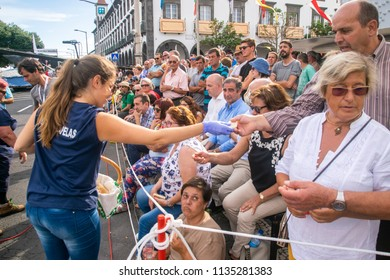 Ponta Delgada, Azores, Portugal - 07/07/2018 - Young girl from Vila das Capelas giving food to the population on the Divine Holy Spirit celebration