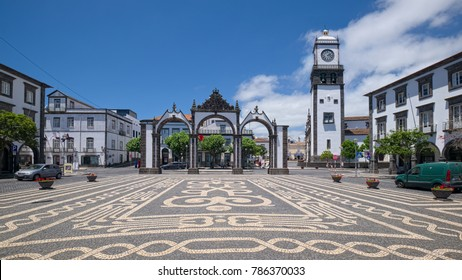 PONTA DELGADA, AZORES, PORTUGAL - JUNE 28, 2017: Historic City Gate (Portuguese: Portas da Cidade) and tower of Church of St. Sebastian in Ponta Delgada city, located on Sao Miguel island of Azores.