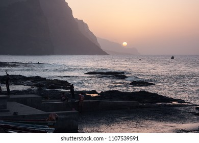 PONTA DO SOL, CAPE VERDE - DECEMBER 08, 2015: Beautiful sunset evening at the rocky shore of Santo Antao Island. People walking and watching the Sun, mountains and the ocean