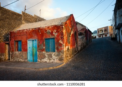 PONTA DO SOL, CAPE VERDE - DECEMBER 08, 2015: Historic house near the port, paint and plaster peeling from the red walls, blue windows.