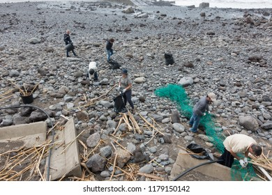 Ponta do Sol, Portugal - March 3, 2018: Local volunteer people cleaning the beach after a storm in Ponta do Sol, Madeira