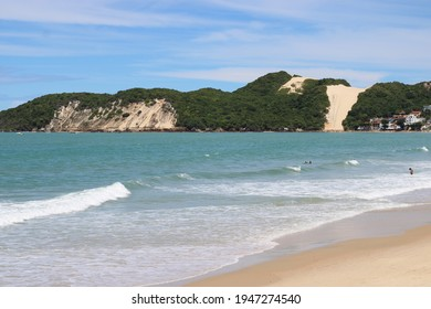 Ponta Negra Beach, Natal, Rio Grande do Norte, Brazil: March 28 2021: The beach of Ponta Negra in a sunny day with some people relaxing on the sand.