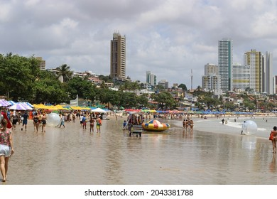 Ponta Negra Beach, Natal, Rio Grande do Norte, Brazil - September 18 2021: The beach in a sunny day. People walking and playing sports. Some buldings are visible on the background.
