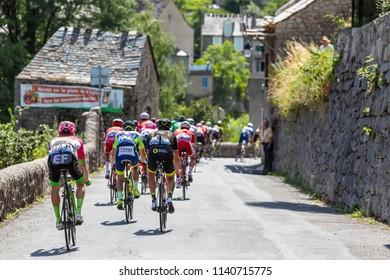 Pont-de-Montvert-Sud-Mont-Lozere, France - July 21, 2018: Rear view of the peloton descending a road in Occitan region during the stage 14 of Tour de France 2018.