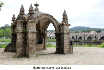 Ponte de Lima, Portugal - July 20, 2021: Guardian Angel Chapel, on the right bank of the river Lima, medieval stone bridge in the background
