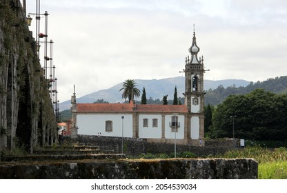 Ponte de Lima, Portugal - July 20, 2021: 18th-century Church of Santo Antonio da Torre Velha, partial view of the medieval stone bridge over the river Lima in the forefront